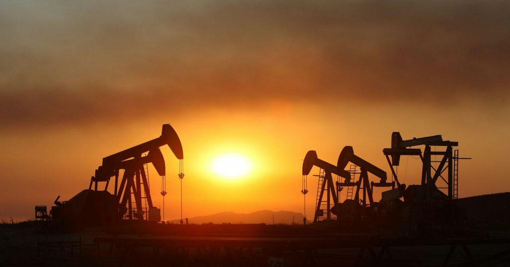 fed rate increase impact on oil industry - pic of oil fields at sunset
